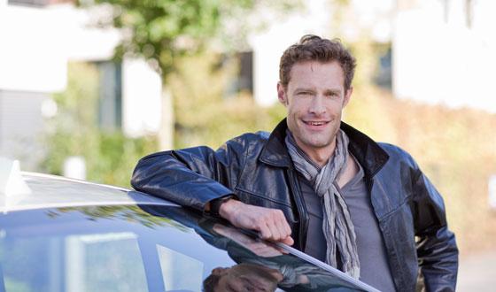 Junger Mann lehnt an Auto